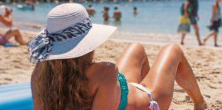 Frau am Strand mit Bikini am Sonnen