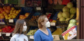 Menschen mit Coronamaske auf der Straße unterwegs