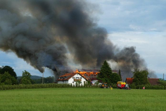 Bauernhof brennt lichterloh über dem Ort ist eine Rauchwolke zusehen