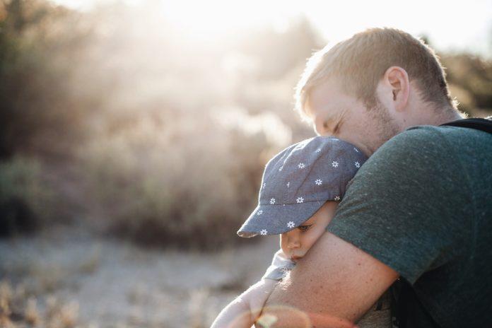 Vater mit Kind auf dem Arm und am kuscheln