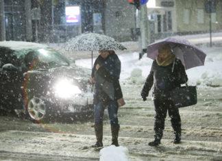 Plötzlicher Schneeinbruch in der Innenstadt mit Menschen