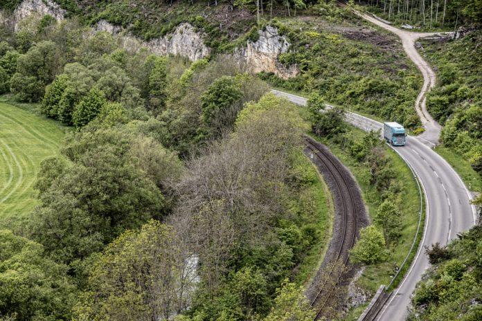 Lkw auf einer Landstraße am fahren neben Bergen