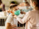 Grundschüler mit gewungenen Coronamasken und Maßnahmen
