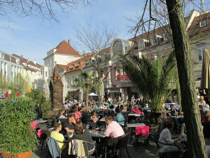 Menschen sitzen entspannt an Außencafes in Karlsruhe